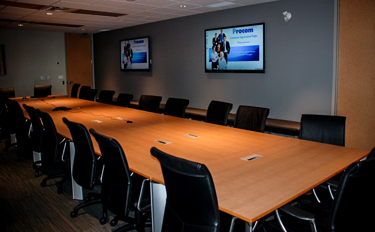 office boardroom with digital signage screens hanging on the walls