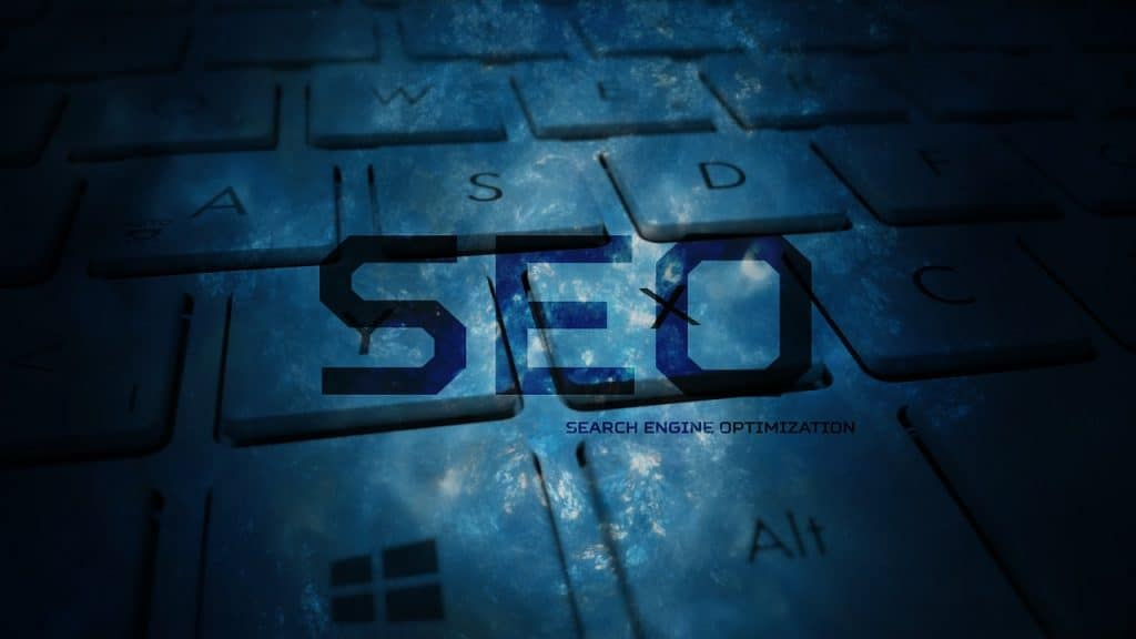 SEO written in the foreground of the image, with computer keyboard faded in the background